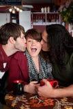 Femme chanceux embrassé par deux hommes beaux Image stock