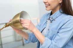 Femme changeant l'ampoule dans la lampe à l'intérieur images stock