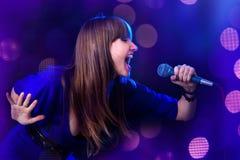 Femme chantant dans le microphone photographie stock