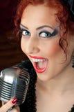 Femme chantant dans le microphone de cru Photo libre de droits