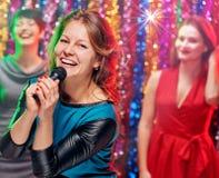 Femme chanteuse de sourire dans le karaoke Image stock