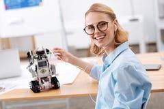 Femme charismatique appréciant la musique avec le robot électronique à l'intérieur Photo stock