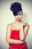 Femme charismatique chique avec la coiffure luxueuse à la mode. Image stock