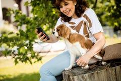 Femme, chien et téléphone portable Photographie stock libre de droits