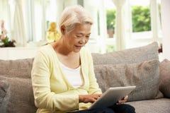 Femme chinois aîné avec l'ordinateur de tablette Photo libre de droits