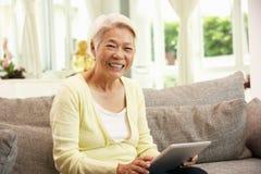 Femme chinois aîné avec l'ordinateur de tablette Image libre de droits
