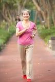 Femme chinois aîné courant en stationnement Photos stock