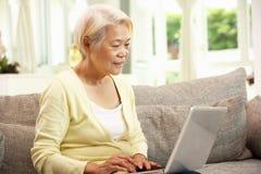 Femme chinoise aînée à l'aide de l'ordinateur portatif tout en détendant Image stock
