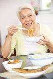 Femme chinoise aînée s'asseyant à la maison mangeant le repas Photographie stock
