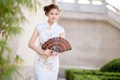 Femme chinoise asiatique dans la prise de chinois traditionnel éventant le papier Image stock