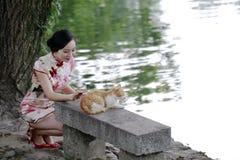 Femme chinoise asiatique dans le jeu traditionnel de cheongsam avec un chat Image libre de droits