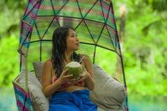 Femme chinoise asiatique heureuse et attirante s'asseyant à l'eau potable accrochante de noix de coco d'hamac détendant à la pisc photos stock