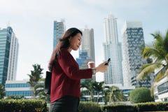 Femme chinoise avec du café de marche et potable de téléphone Photo stock