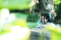 Femme chinoise dans la montée bleue et blanche traditionnelle de robe de Hanfu au-dessus de la table en pierre photographie stock libre de droits