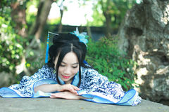 Femme chinoise dans la montée bleue et blanche traditionnelle de robe de Hanfu au-dessus de la table en pierre photos stock