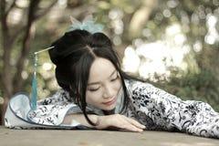 Femme chinoise dans la montée bleue et blanche traditionnelle de robe de Hanfu au-dessus de la table en pierre photo libre de droits