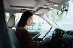 Femme chinoise occupée d'affaires travaillant dans la voiture avec des papiers Photo libre de droits