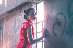 Femme chinoise seule regardant la lumière sur les fenêtres avec tristesse photo stock