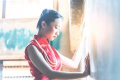 Femme chinoise seule regardant la lumi?re sur les fen?tres avec tristesse photos stock