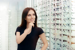 Femme choisissant des cadres de lunettes dans le magasin optique Photographie stock