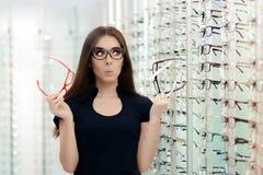 Femme choisissant des cadres de lunettes dans le magasin optique Photographie stock libre de droits