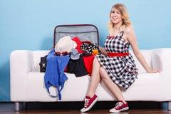 Femme choisissant des choses pour emballer dans la valise Photo stock