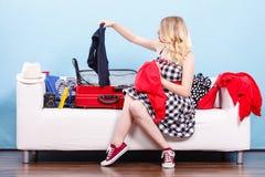 Femme choisissant des choses pour emballer dans la valise Photos stock