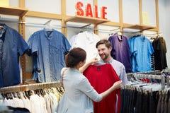 Femme choisissant des vêtements pour le mari images libres de droits