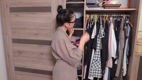 Femme choisissant des vêtements pour porter et la pensée clips vidéos