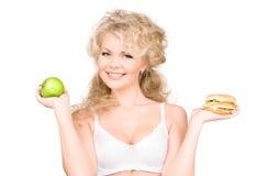 Femme choisissant entre l'hamburger et la pomme Images libres de droits
