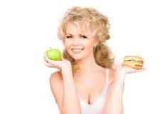 Femme choisissant entre l'hamburger et la pomme Photos libres de droits