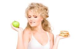 Femme choisissant entre l'hamburger et la pomme Image libre de droits