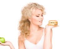 Femme choisissant entre l'hamburger et la pomme Image stock