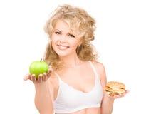 Femme choisissant entre l'hamburger et la pomme Photographie stock libre de droits
