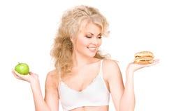 Femme choisissant entre l'hamburger et la pomme Images stock