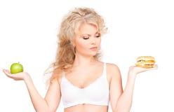 Femme choisissant entre l'hamburger et la pomme Photo stock