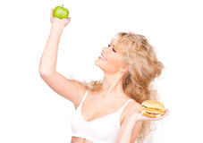 Femme choisissant entre l'hamburger et la pomme Photographie stock
