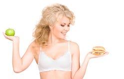 Femme choisissant entre l'hamburger et la pomme Photo libre de droits