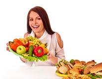 Femme choisissant entre le fruit et l'hamburger Photo libre de droits