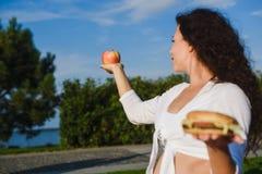 Femme choisissant entre un hamburger et une pomme Image libre de droits