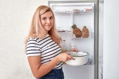 Femme choisissant la nourriture dans le réfrigérateur à la maison photographie stock libre de droits