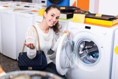 Femme choisissant la nouvelle machine de blanchisserie photos stock