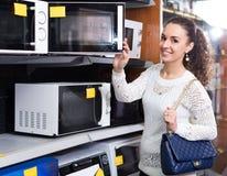 Femme choisissant la nouvelle micro-onde images stock