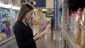 Femme choisissant le détergent de blanchisserie dans l'épicerie Femme d'affaires dans le supermarché clips vidéos