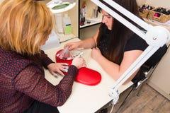 Femme choisissant le modèle pendant pendant la manucure de gel Image stock
