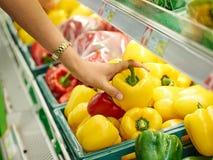 Femme choisissant le poivron doux jaune Image libre de droits