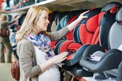 Femme choisissant le siège de voiture d'enfant Photos libres de droits