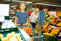 Femme choisissant les fruits saisonniers Image libre de droits