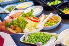 Femme choisissant les ingrédients végétaux au comptoir à salades Photographie stock libre de droits