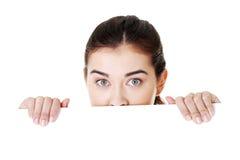 Femme choqué retenant le panneau blanc Photographie stock